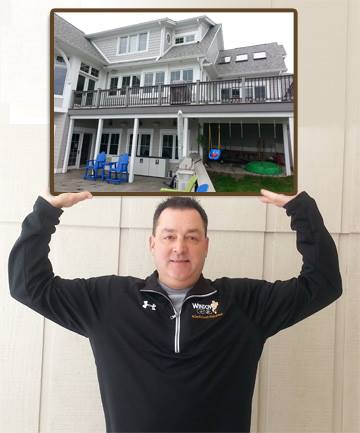 Mike Angle of Window Genie Indy holds a picture of his franchise's recent completed work on a home.